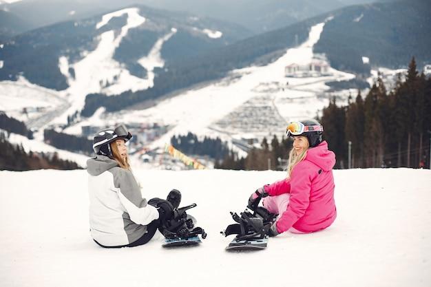 Mulheres em traje de snowboard. mulheres do esporte em uma montanha com uma prancha de snowboard nas mãos no horizonte. conceito em esportes