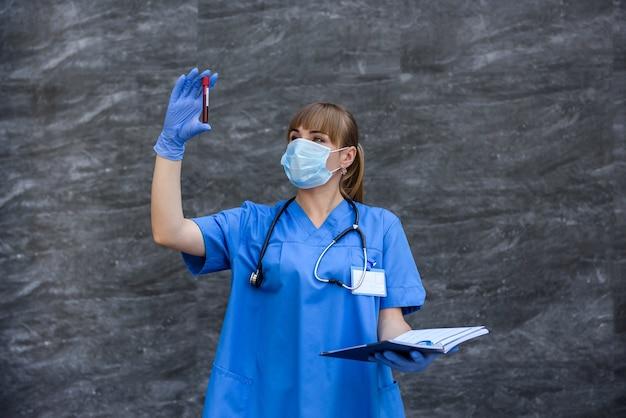 Mulheres em uniforme médico posando com tubos de ensaio com substância vermelha