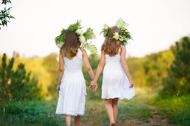 Mulheres em vestidos de algodão branco, com cabelos longos e lisos, apreciam a vida, agitam e dançam em um campo de flores amarelas na luz quente do pôr do sol