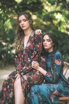 Mulheres em vestidos florais cercados pela natureza