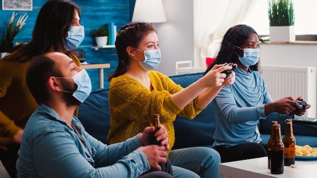 Mulheres empolgadas jogadoras multirraciais sentadas no sofá jogando videogame no console durante a nova festa normal usando máscaras de proteção