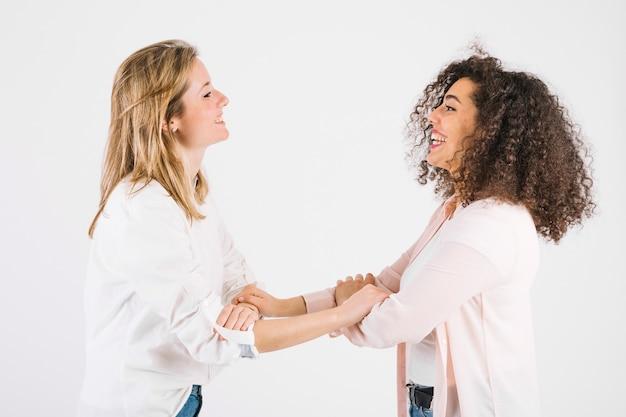 Mulheres encantadoras agarrando braços