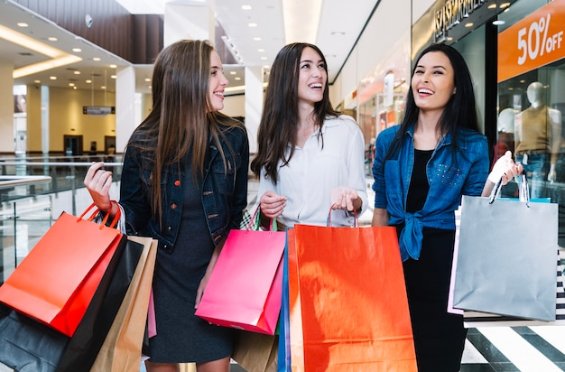 Mulheres encantadoras andando com bolsas de papel