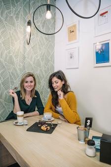 Mulheres encantadoras comendo bolo no café