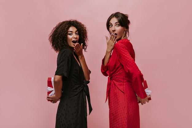 Mulheres encantadoras surpresas com um penteado estiloso em uma roupa elegante e brilhante, olhando para a câmera e segurando pequenas caixas de presente atrás