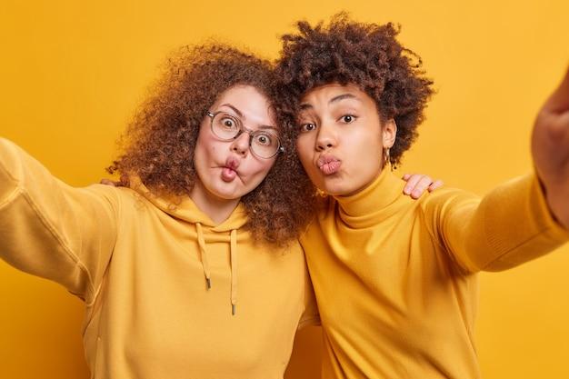 Mulheres engraçadas de raça mista se abraçam e fazem careta, mantém os lábios dobrados no beijo, fazem lábios de peixe bobos, vestidos com roupas amarelas, fazem selfie ter relacionamentos amigáveis. amizade