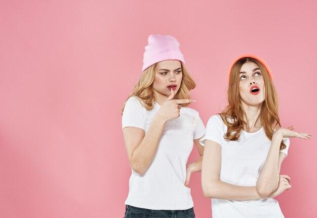 Mulheres engraçadas em camisetas glamourosas, chapéus recortados, vista de fundo rosa