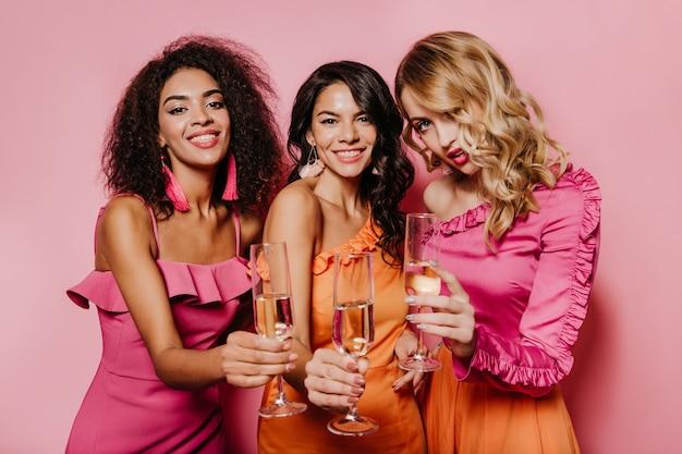 Mulheres entusiasmadas em vestidos curtindo o evento