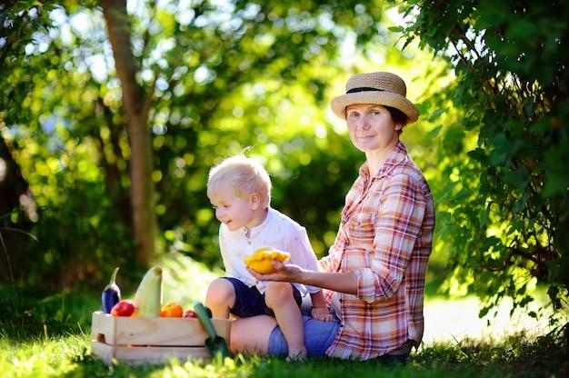 Mulheres envelhecidas médias bonitas e seu neto pequeno adorável que apreciam a colheita.