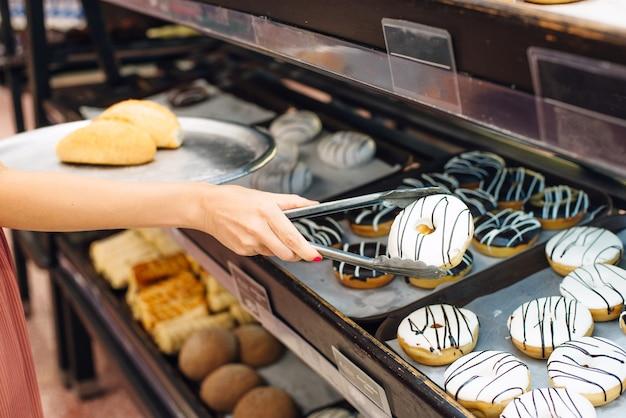 Mulheres escolhendo donut no supermercado. pinças para pães e bandeja.