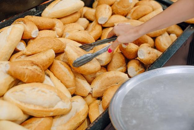 Mulheres escolhendo pão no supermercado. pinças para pães e bandeja.