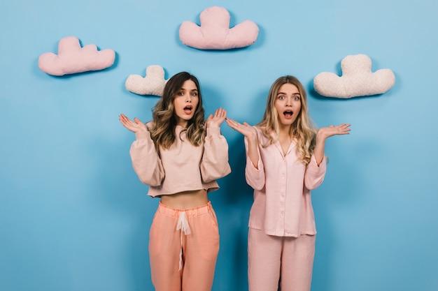Mulheres espantadas com pijamas fofos posando com as mãos para cima