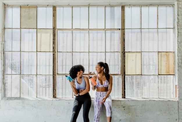 Mulheres esportivas conversando em uma academia enquanto bebem água