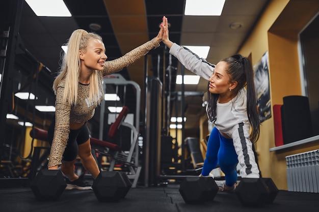 Mulheres esportivas dando high five umas nas outras enquanto malham juntas na academia