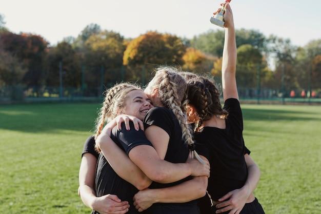Mulheres esportivas felizes, abraçando uns aos outros