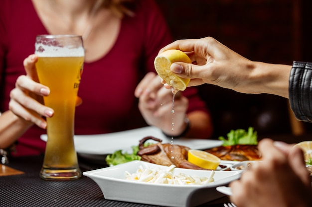 Mulheres espremendo limão em cima de lanche de cerveja com queijo