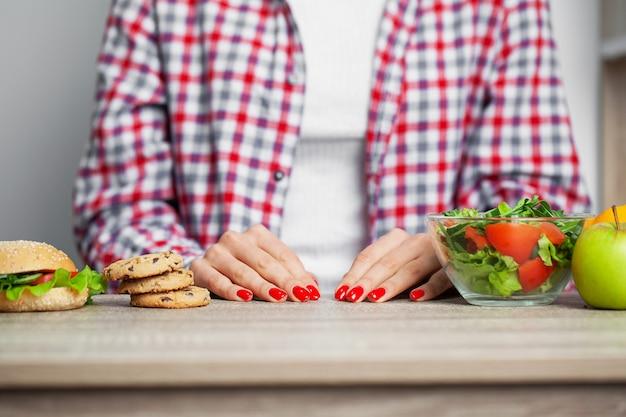 Mulheres está escolhendo a opção entre hambúrguer e salada durante sua sessão de dieta