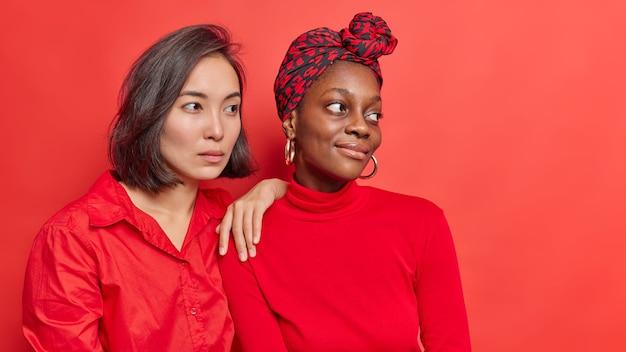 Mulheres estão próximas umas das outras, distantes, pensando na vida futura, sonhando acordadas, vestidas com roupas casuais isoladas no vermelho