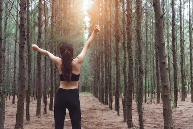 Mulheres, esticando os braços e respirando ar fresco no meio do pinhal