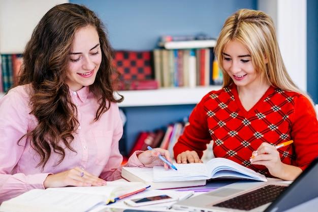 Mulheres estudam juntas e sorrindo