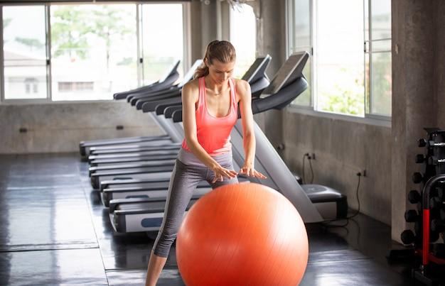 Mulheres exercitam com bola no ginásio de fitness