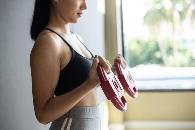Mulheres exercitando com duas placas de peso com halteres