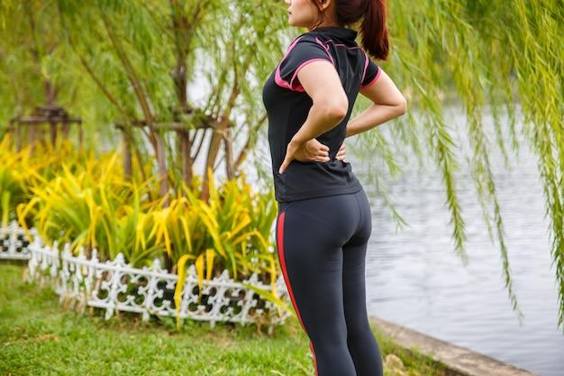 Mulheres exercitando. mulher nova da aptidão que exercita de manhã no parque público.