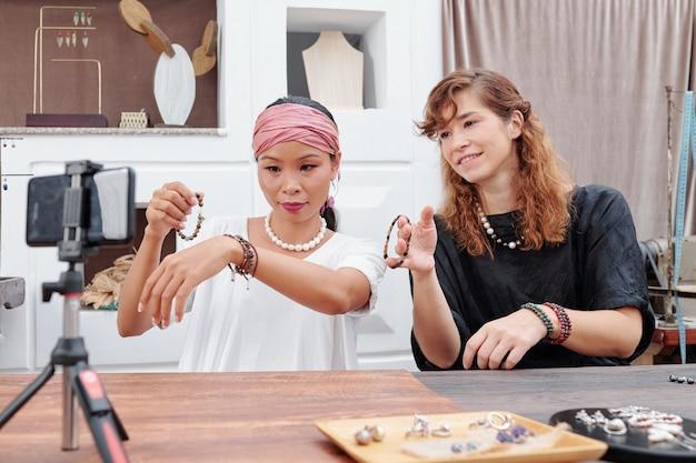 Mulheres exibindo pulseiras feitas à mão