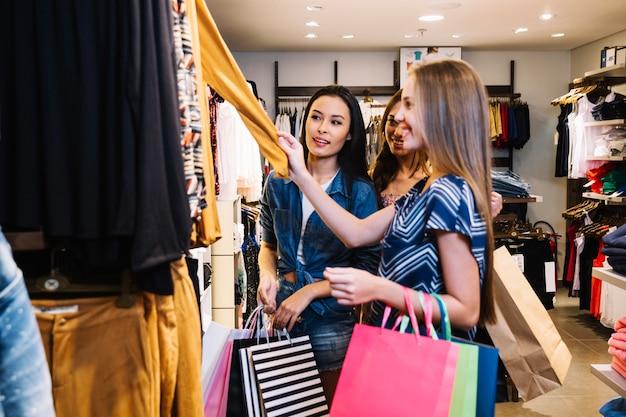 Mulheres explorando roupas na loja