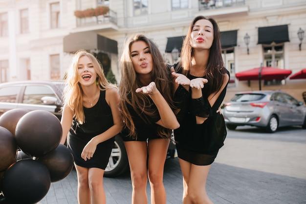 Mulheres fascinantes em vestidos curtos mandando beijos no ar na frente de um grande prédio