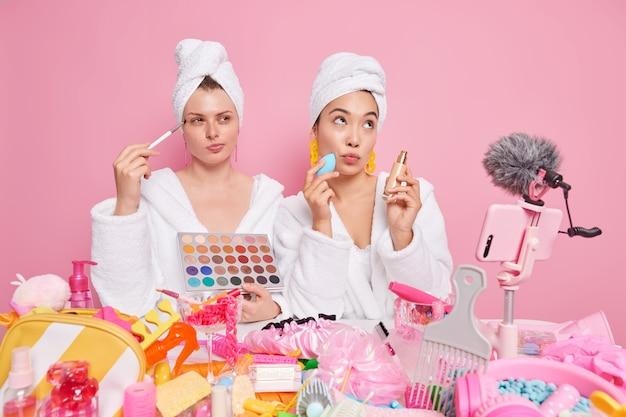 Mulheres fazem maquiagem, usam produtos cosméticos, fazem revisão, recorde, vídeo tutorial sobre como cuidar de si mesmo, use roupões de banho macios e brancos posar na frente do smartphone