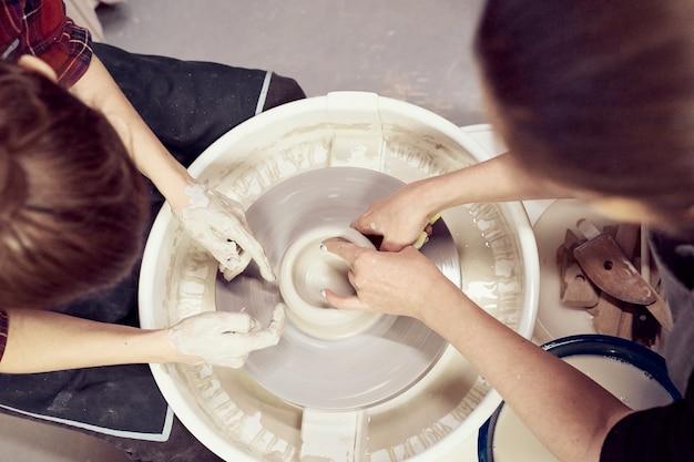 Mulheres fazendo cerâmica, conceito de oficina e master class, close-up de quatro mãos