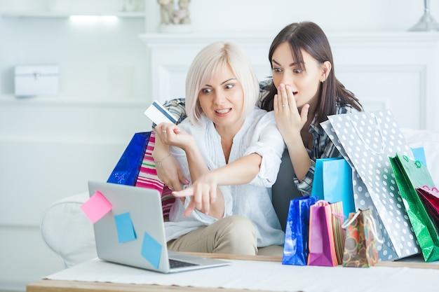 Mulheres fazendo compras online. mulher no laptop com sacolas de compras