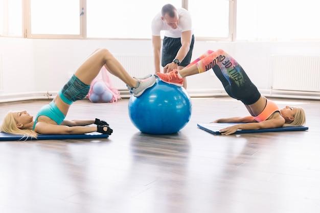 Mulheres fazendo exercícios usando fitball com treinador
