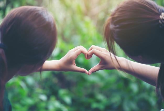 Mulheres fazendo formas de coração com as mãos