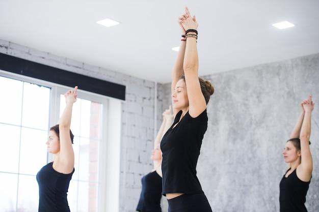 Mulheres fazendo pose de saudação ao sol para ioga em um estúdio de ioga