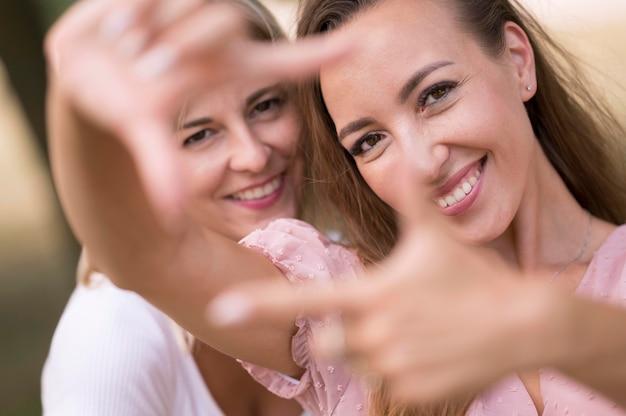Mulheres fazendo uma moldura com os dedos