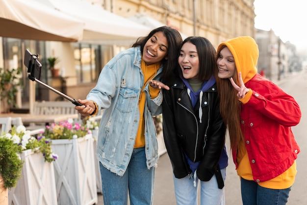 Mulheres fazendo uma selfie usando um bastão de selfie