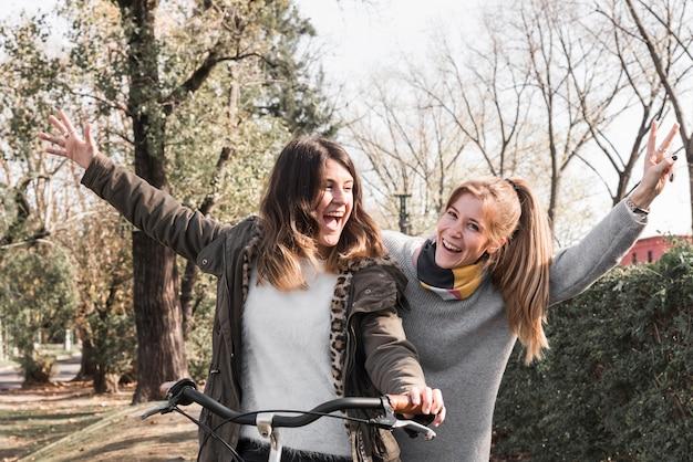 Mulheres felizes andando de bicicleta no parque