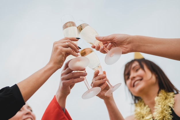 Mulheres felizes animando taças de champanhe na festa no terraço