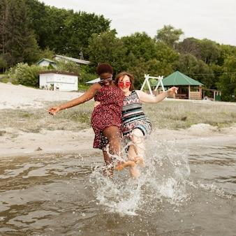 Mulheres felizes brincando com água na praia