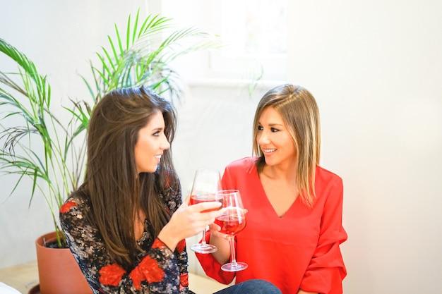 Mulheres felizes, brindando e torcendo copos de vinho tinto no apartamento
