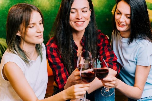 Mulheres felizes, brindando vinho na festa