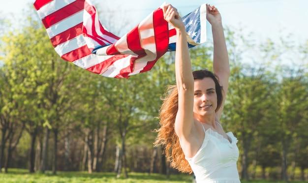 Mulheres felizes com a bandeira americana nos eua comemoram 4 de julho