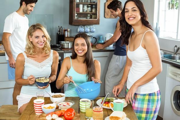 Mulheres felizes com amigos homens cozinhando na cozinha em casa