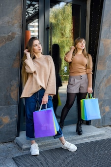 Mulheres felizes com sacolas de compras coloridas posando ao ar livre