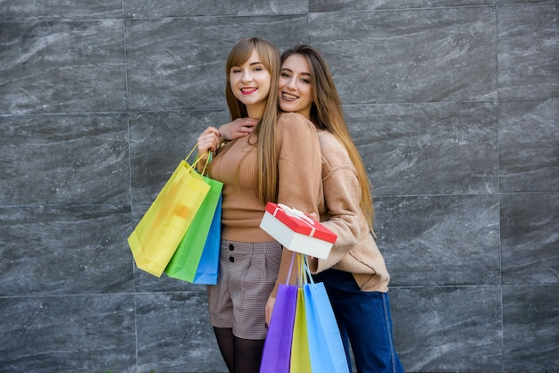 Mulheres felizes com sacolas de compras em casacos de pele posando na rua da cidade