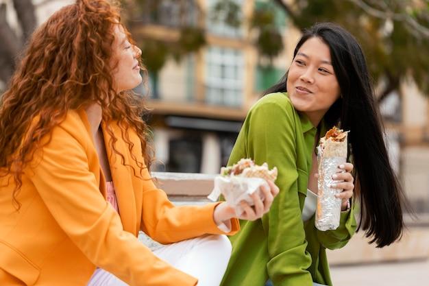 Mulheres felizes comendo comida de rua juntas