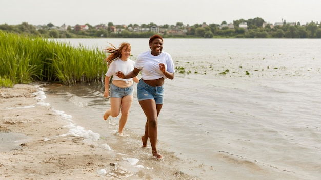 Mulheres felizes correndo juntas na praia