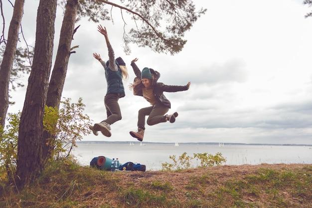 Mulheres felizes dos viajantes que saltam.